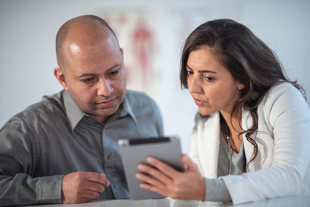 Mulher segurando tablet e mostrando a um homem
