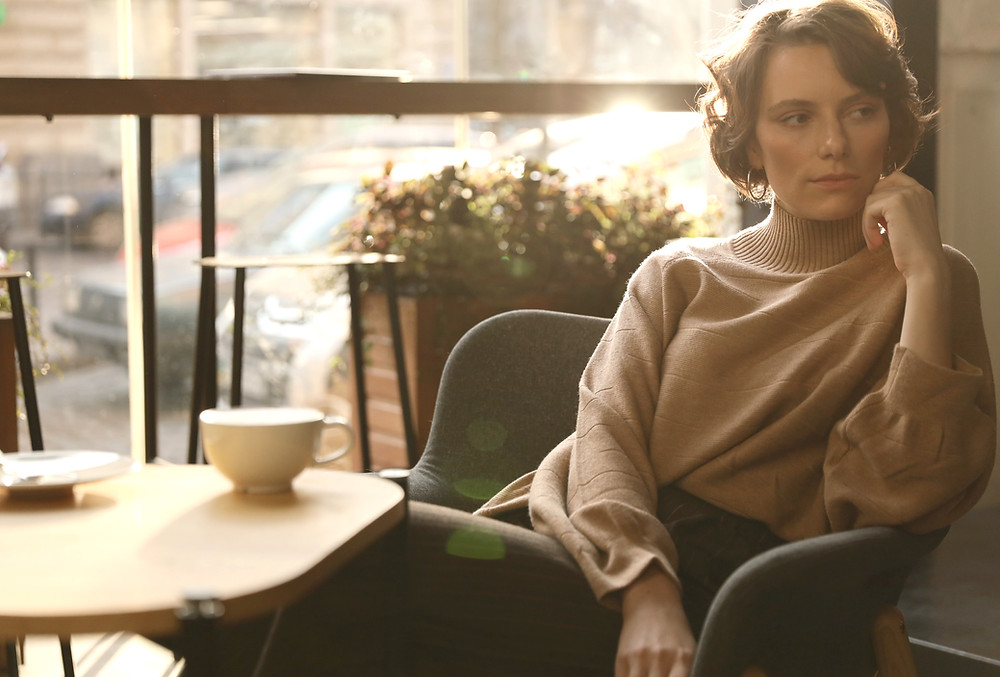 Woman in soft, pale brown turtle-necked jumper sitting pensively in a chair.