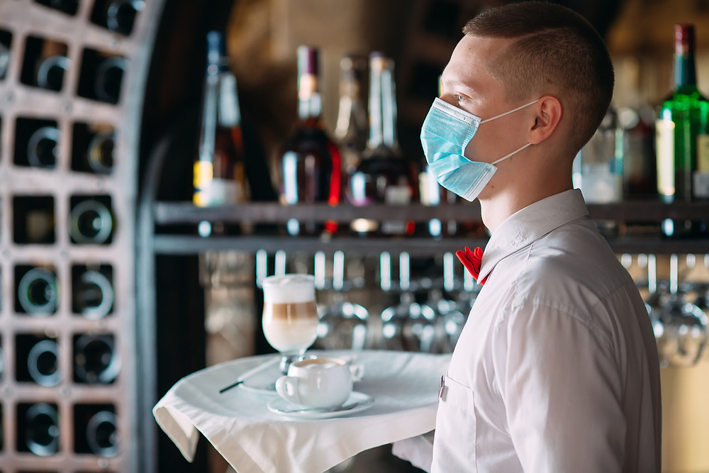 Masked waiter serving a drink on a tray