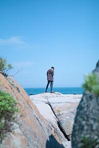 海辺にたたずむ男性