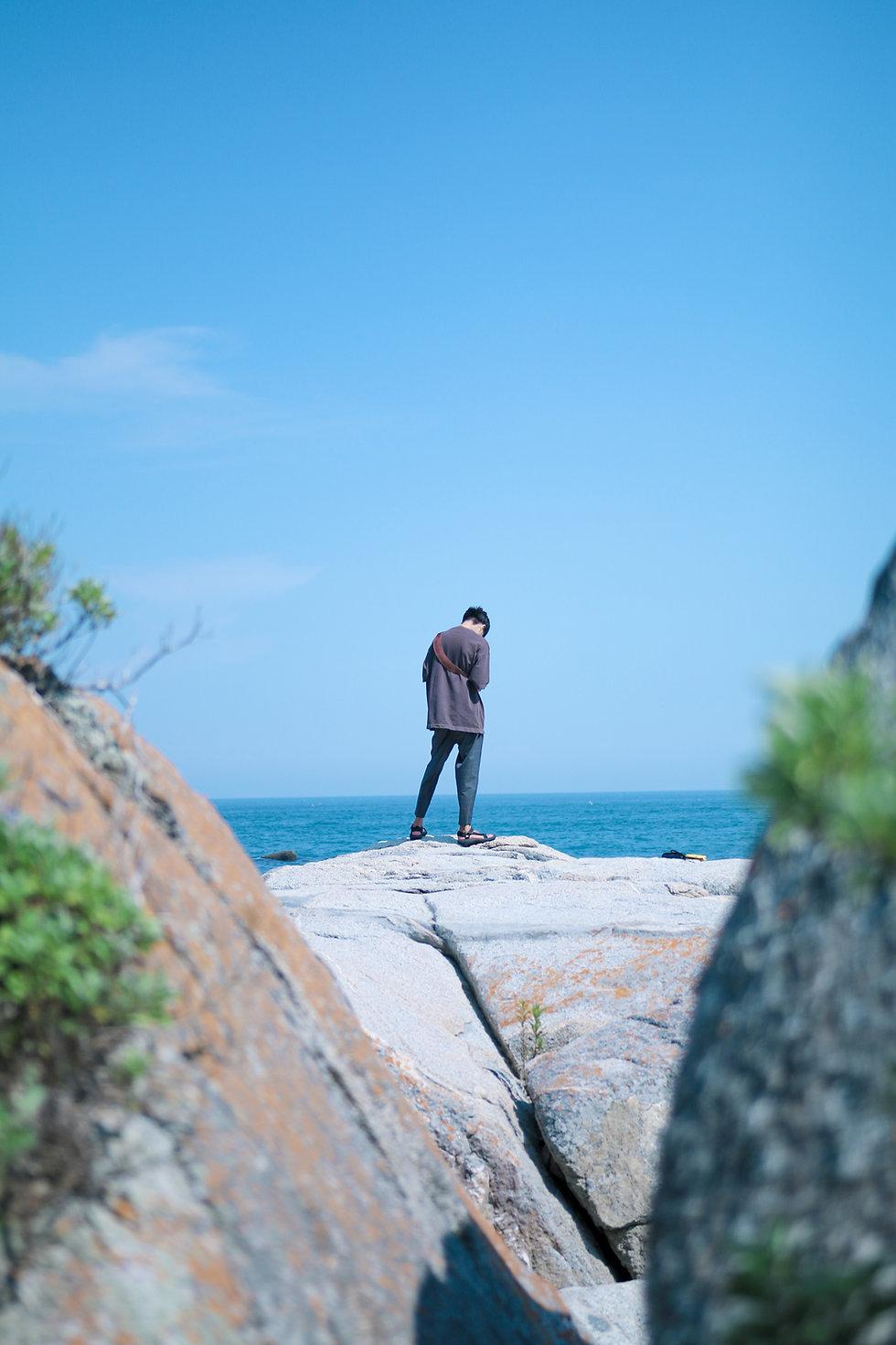 Homem de pé à beira-mar