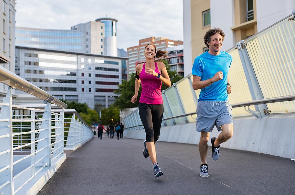 Homem de blusa azul e mulher de blusa rosa correndo