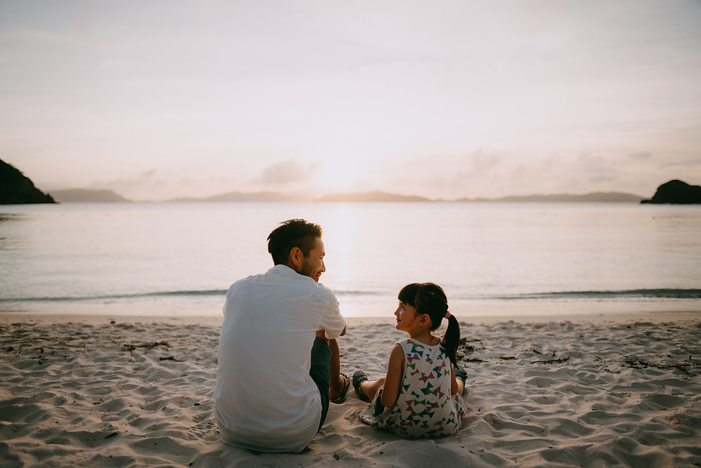 A man and a little girl sat on a white sandy beach in front of a still ocean looking into each other's eyes