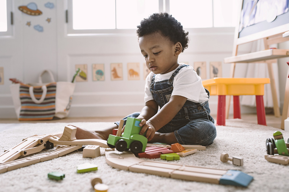 Black child playing with wooden toys