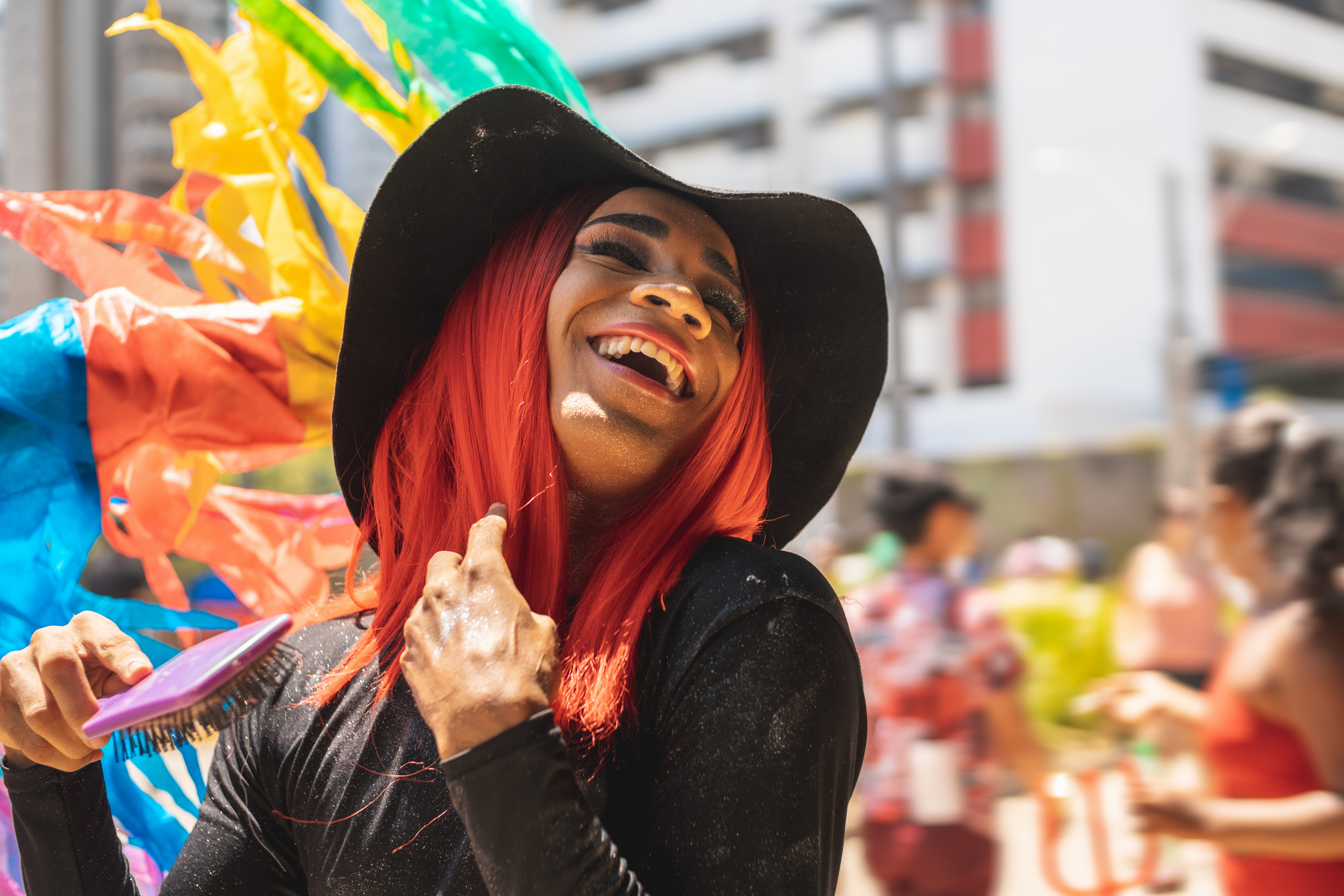 A queer person throws their head back smiling at a gay pride parade