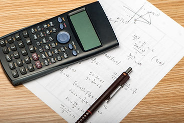 Calculator with mathematical problems written on paper.