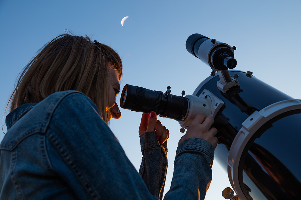 Woman looking at sky through a telescope