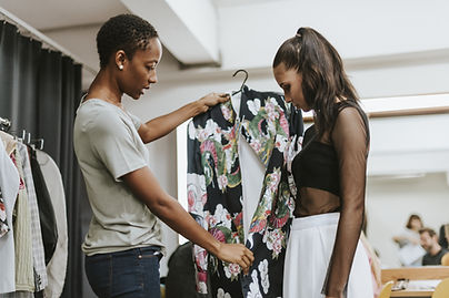 A young female trying on clothes with the assistance of a fashion stylist in Cardiff, South Wales