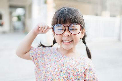 Criança pequena com óculos grandes