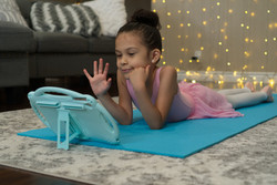 Young girl holding up 5 fingers to a tablet while laying on the floor in a ballet costume.