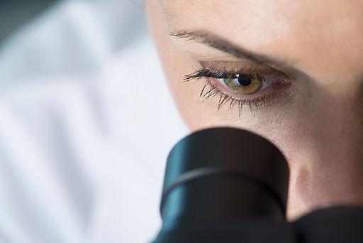 Scienziato che utilizza microscopio