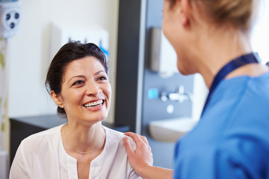 Patient talking to doctor in or follow-up cancer care and is haapy with the results.
