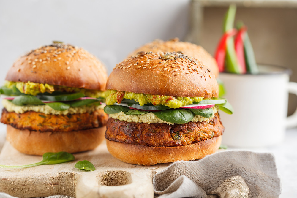 photo shows two vegan burgers on a wooden board. The buns are brown with yellow sauce and green salad.