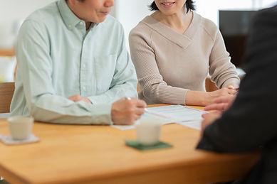 中年夫婦に説明するビジネスマン