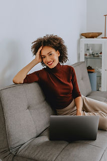 A young smiling lady sitting on a couch working from Home, laptop on the couch. Her right elbow is resting on back of couch and her trunk is twisted.