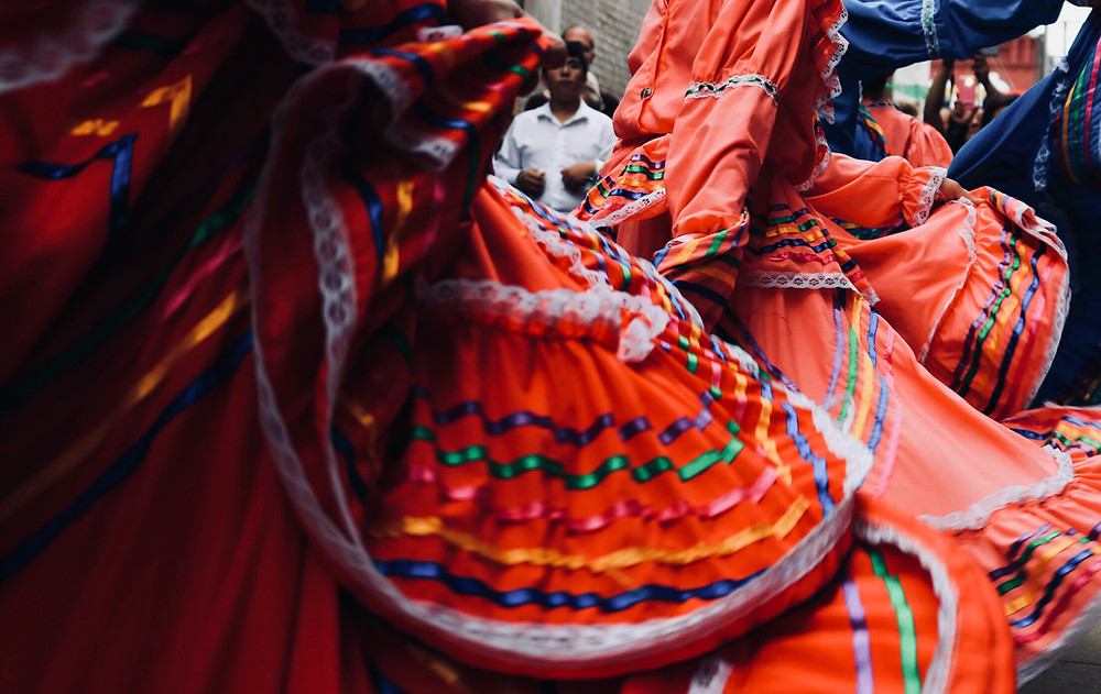 This is a picture of a bunch of women in folklorico dresses. They are all very close to the camera, which hides the women's faces. All but one of the dresses are in shades of pink, and the remaining dress is a periwinkle blue. The skirts on the dresses are full, and they're decorated with purple, green, pink, yellow, and blue ribbon, as well as white lace.