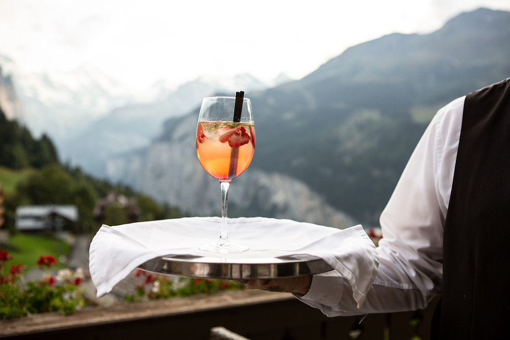 Waiter serving drink with alcohol