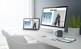 A calm home office with a white desk and chair and an open laptop and a larger screen both showing website screens. Suggestion of Responsive Website Design. A white keyboard, a grey cup, a mobile phone, and a tablet or iPad can also be seen.