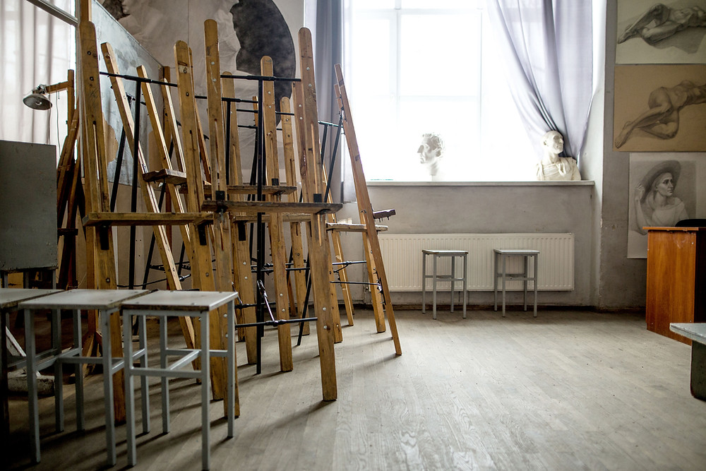 An empty artist's studio with paint easels, sketches and busts.