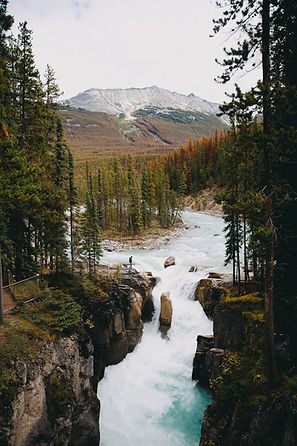 Rushing river nestled in a valley below a snowcapped mountain