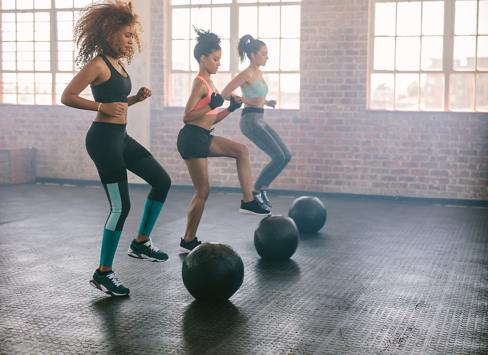 three woman exercising with medicine balls