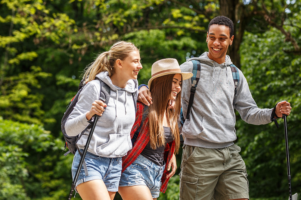 Image of two girls and boy hiking in wooded area. First woman is wearing a gray sweatshirt and denim shorts with long blonde hair. Second woman is wearing a red plaid shirt and denim shorts with long brown hair and a hat.  Man is wearing gray shirt and brown shorts.  They are smiling and having fun on their hike.