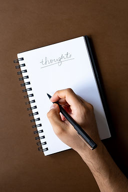 A hand holding a pen and writing on paper