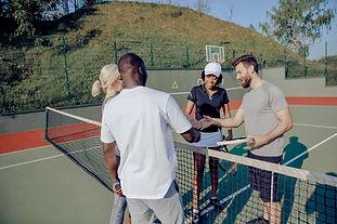 Jugadores de tenis estrechándose las man