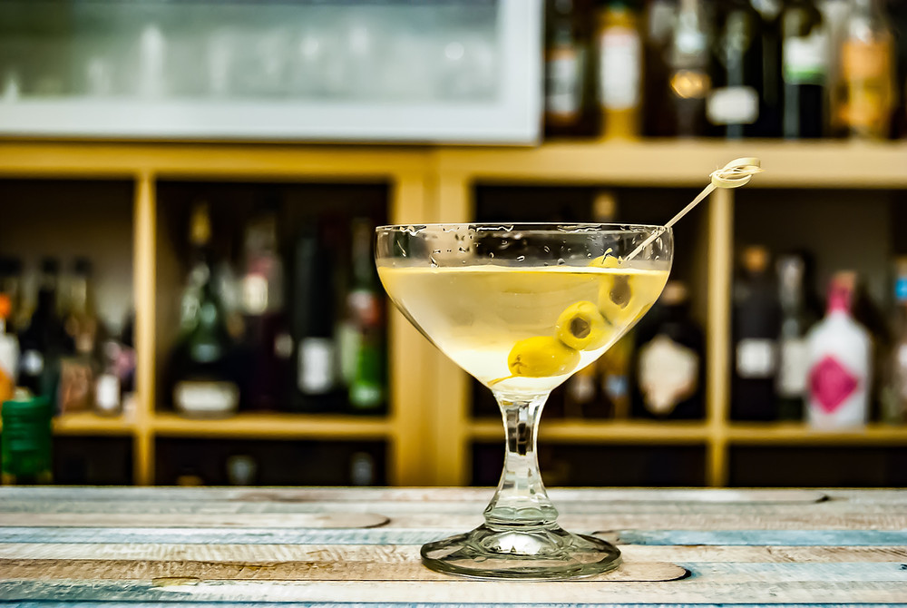 Martini sitting on a bar with olives on the toothpick.