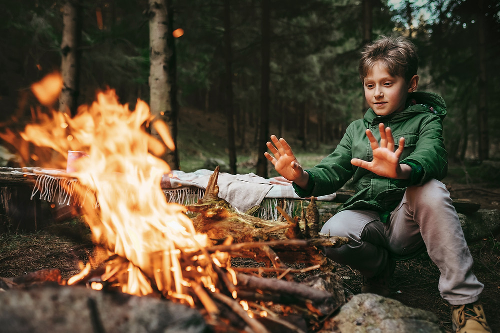 Child camping with a campfire