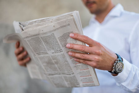 Photo of a hand of a male that holds a newspaper