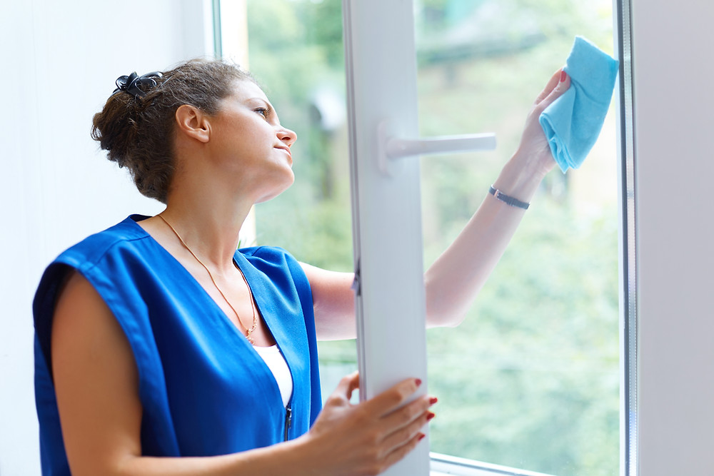Lady cleaning home windows with a cloth