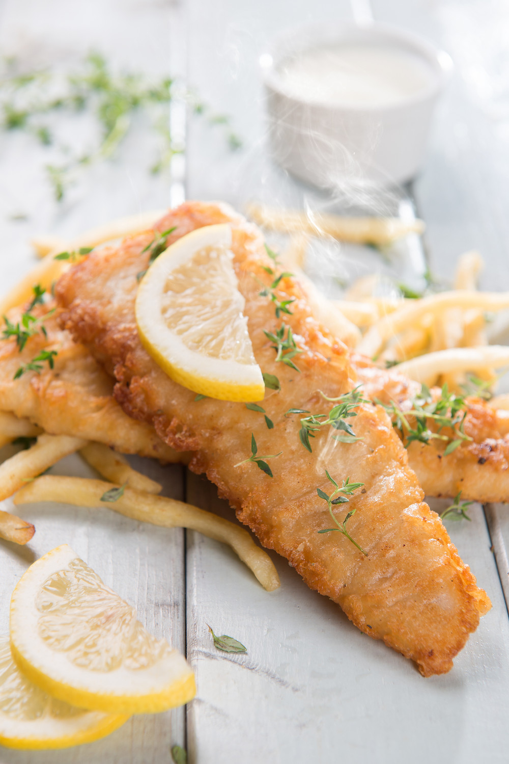 Deep fried and battered fish, chips and a slice of lemon