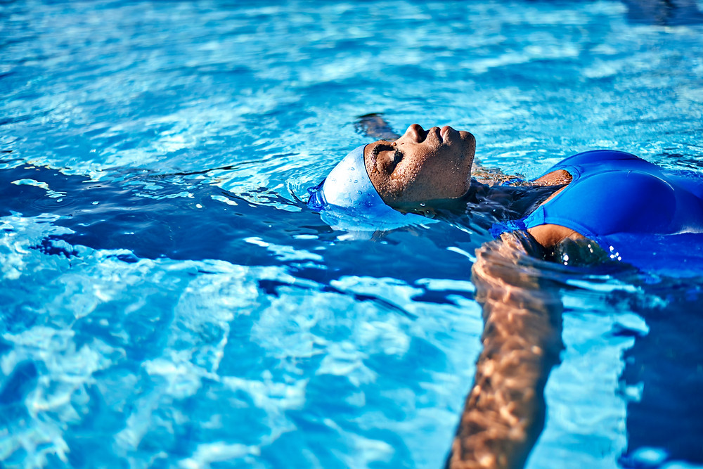 A lady floats on her back in swimming pool wearing blue swimming costume. Swimming benefits the mind and body.