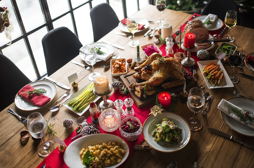 Christmas dinner spread on wooden table and red linen with turkey