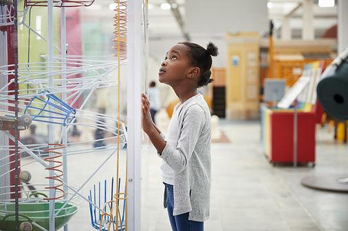 Uma menina olhando para um modelo de fís