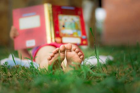 Criança lendo na grama