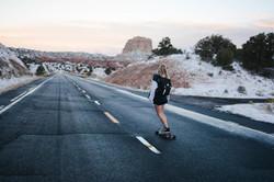 woman skating down a desert road