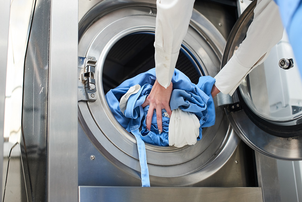 Putting clothes and linens into the washing machine
