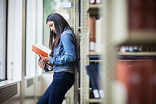 Une femme lisant un livre appuyée sur mur. Scène extérieur.