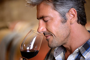 Uomo che sente l'odore del vino