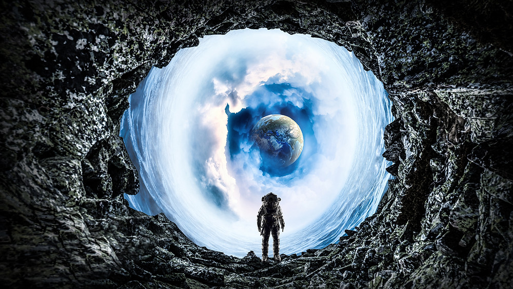 An astronaut standing in a cave-like structure with a view of a planet that's surrounded by clouds.