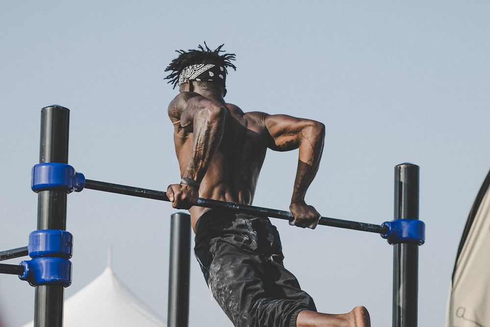 man performing triceps dips on a pull-up and dip station