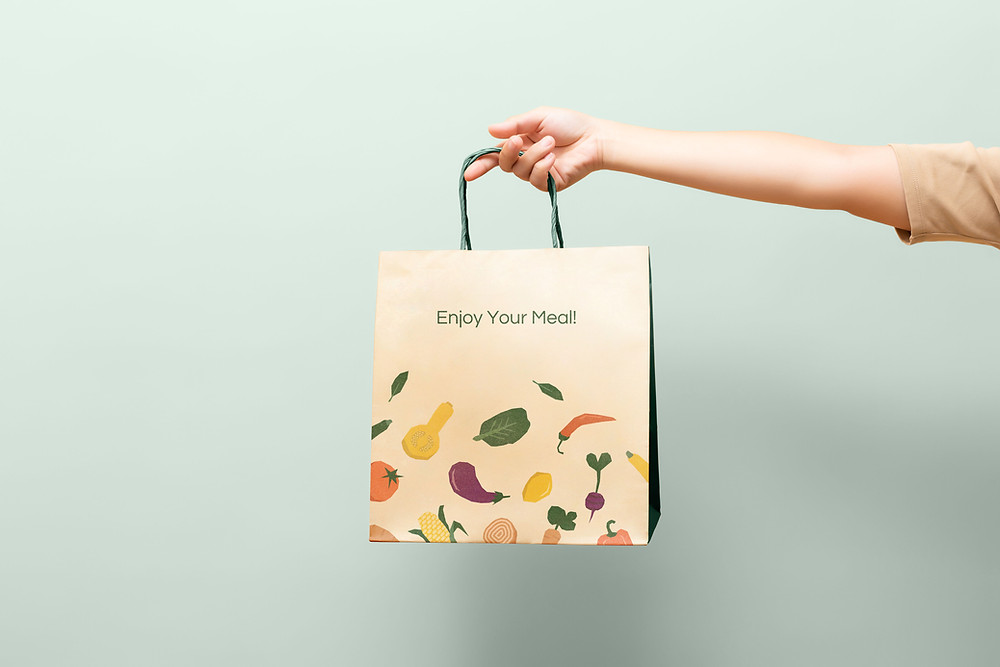 Someone holding a food delivery bag saying Enjoy Your Meal