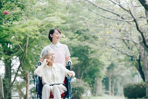 公園を散歩するシニアとヘルパー 車椅子