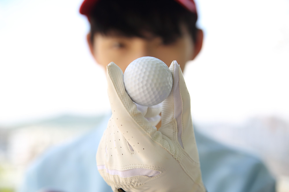 Asian golf player holding a golf ball towards the camera lens