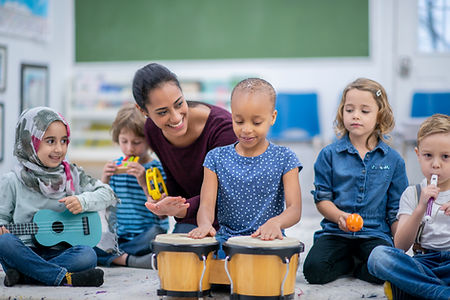 adult smiling and encouraging a child playing bongos with other children playing ukulele, shakers and pipes