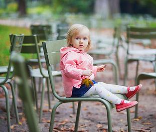 Petite fille sur une chaise verte