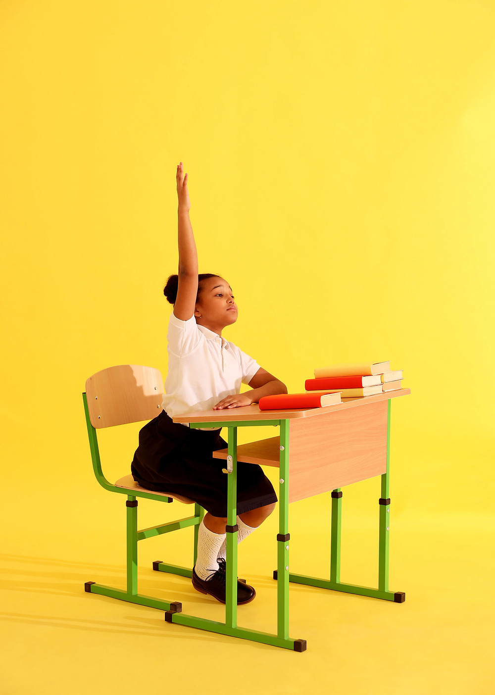 A girl sitting at a desk raising her hand enthusiastically.