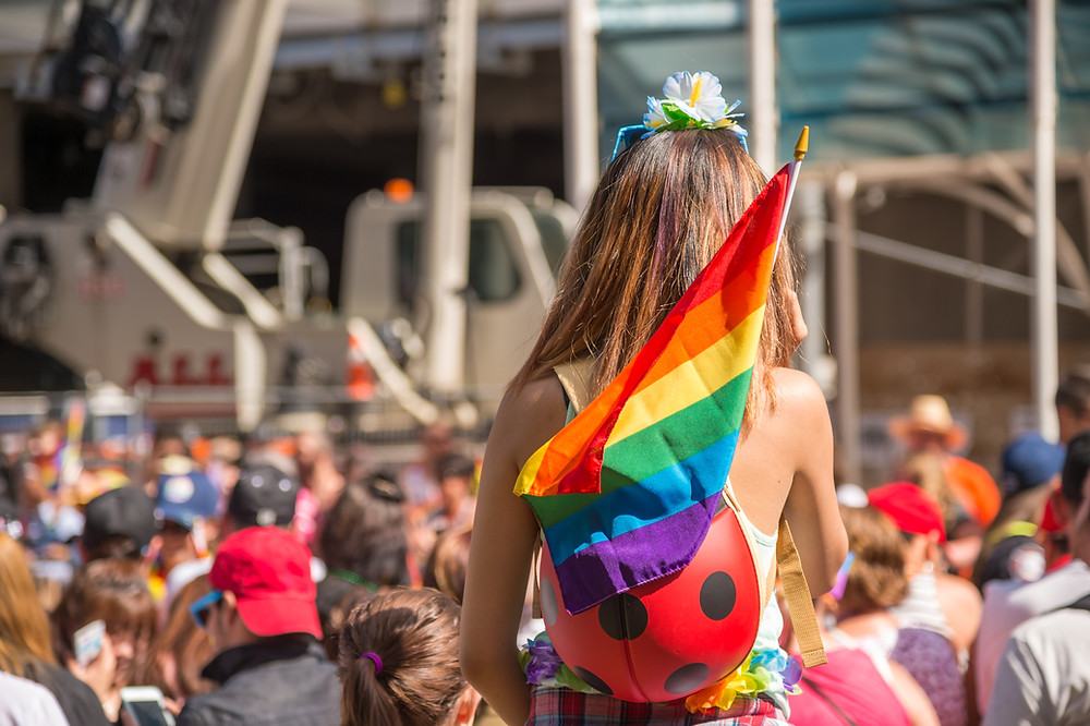 A young woman with the Rainbow flag at a Pride parade.